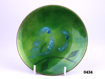 Mid century enamel on copper small plate with two birds on a branch by American enamel artist Judith Wedemeier (Pre-marriage to Norman Howard Brumm) Background colour in an iridescent like shades of green with birds accentuated in pale blue Signed Wedemeier USA to base Measures 125mm in diameter