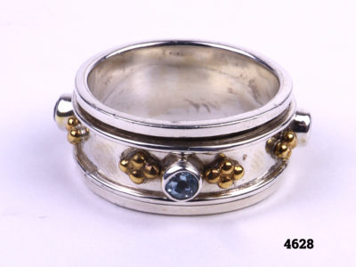 Silver Ring with spinning mid section adorned with small pale blue stones and gilt decoration