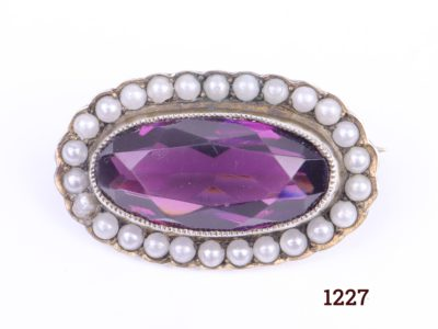 Edwardian silver petite brooch with oval cut amethyst coloured stone surrounded with seed pearls Main photo showing the front view of brooch