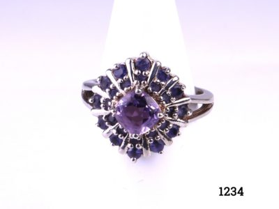 925 Sterling silver ring with princess cut amethyst stone to the centre surrounded by 12 small round lazulite stones. Size N / 6.75. Main photo showing front view of ring displayed on a stand.