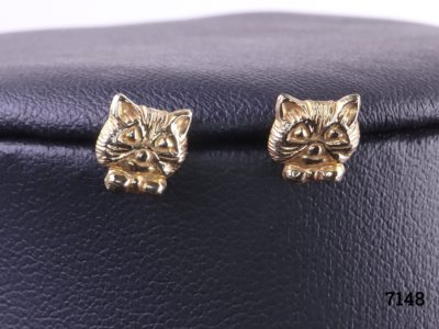 9 Carat gold cat stud earrings featuring the head of a cat with bow tie on each earring. Butterfly back fastening. Very small and fiddly Main photo showing close up of both cat stud earrings with visible details of cats features