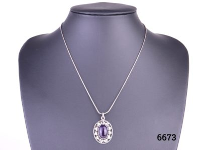 925 Sterling silver and amethyst cabochon pendant on a sterling silver snake chain Pendant drop length 32mm and Chain measures 405mm long. Weight 9.4g. Main photo of necklace displayed on a stand.