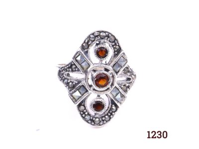 Silver and garnet ring. 925 Sterling silver ring set with three garnets and marcasite in an Art Deco style. Size R / 8.5. Ring front measures 25mm by 22mm. Main photo showing front of ring