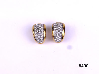 Vintage Swarovski clip-on earrings in gilt metal encrusted with Swarovski crystals Measures 20mm by 10mm Both clips in good order Main photo of earrings displayed on a flat surface showing crystals