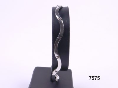 Wavy sterling silver bracelet in a Modernist style with solid links. Hallmarked 925 for sterling silver Main photo showing bracelet displayed on stand straight on view